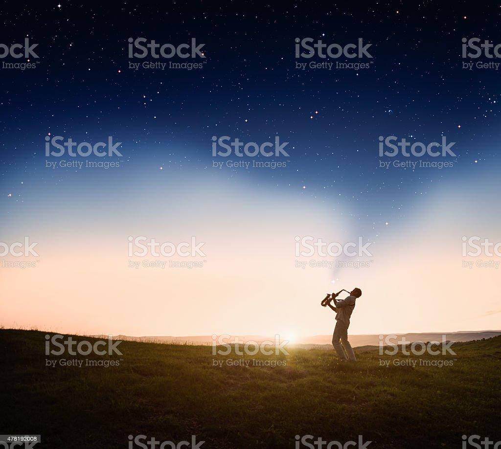 Man playing a saxophone at sunset stock photo