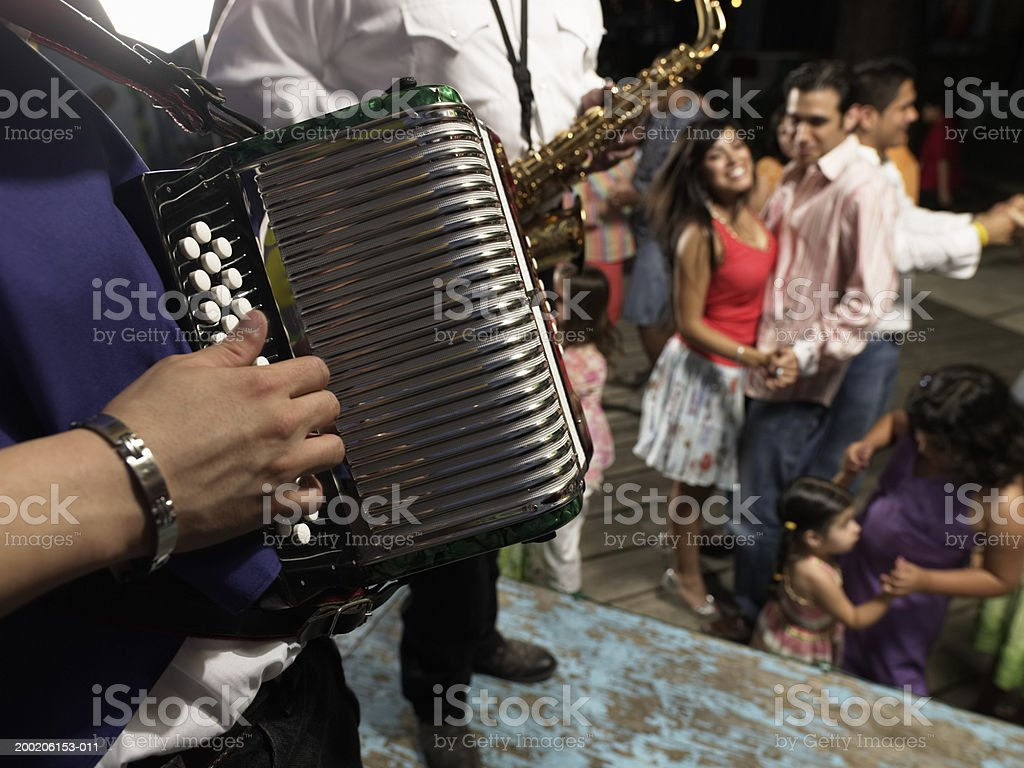 Man playing accordion, people dancing in background stock photo