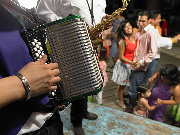 man playing accordion, people dancing in background - accordion stock photos and pictures