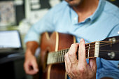 istock Man playing acoustic guitar at home 596568503