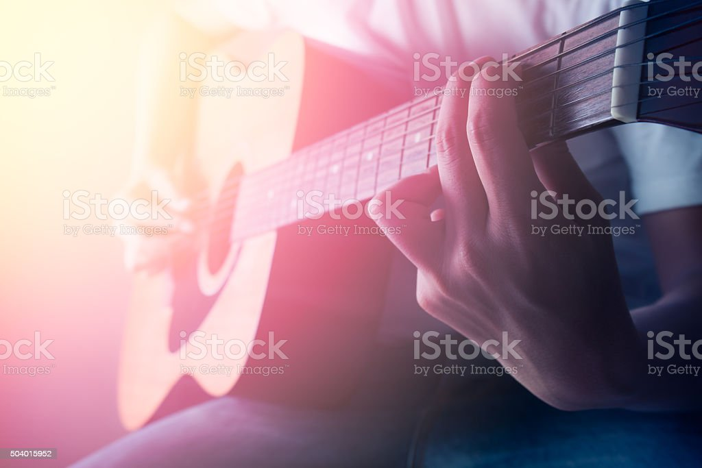 Man playing acoustic guitar in concert stock photo