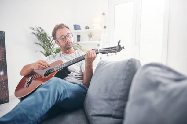 Mann spielt Akustikgitarre im Wohnzimmer. – Foto