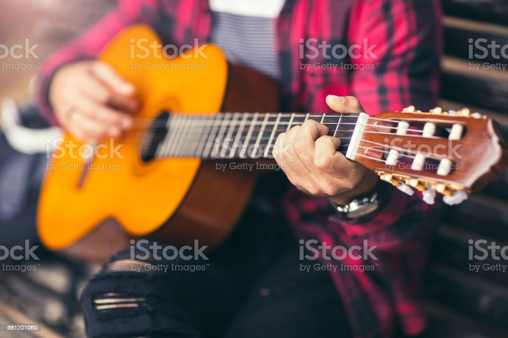 Man playing acoustic guitar on a park bench royalty-free stock photo