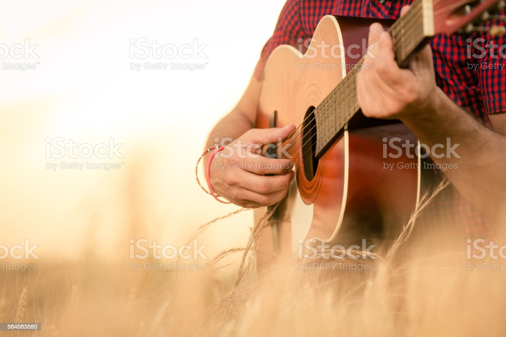 Man playing acoustic guitar on the field stock photo