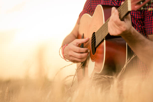 Man playing acoustic guitar on the field Close up of male hands playing acoustic guitar on the wheat field at the sunset. Retro, music, lifestyle concepts. country and western music stock pictures, royalty-free photos & images