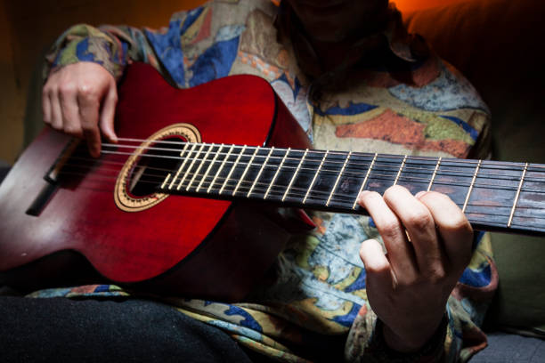 Man playing acoustic guitar. Faceless shot of a guitar performer while plays an acoustic guitar with vintage colorful shirt on a dark and warm background. Flamenco music guitarist playing concept. romani people stock pictures, royalty-free photos & images