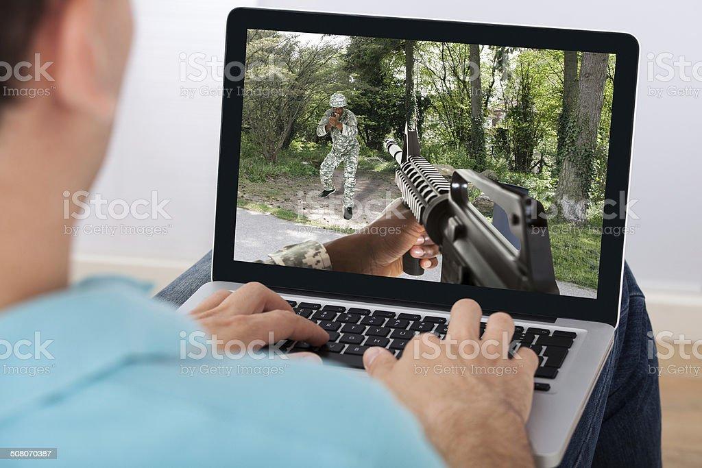 Man Playing Action Game On Laptop stock photo