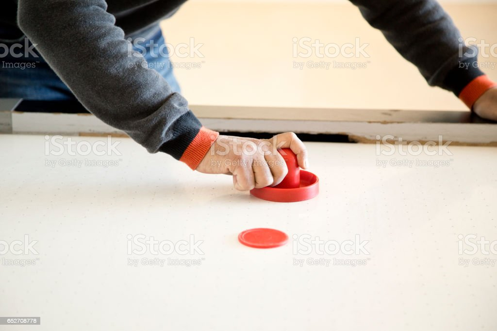 Man playing air hockey stock photo
