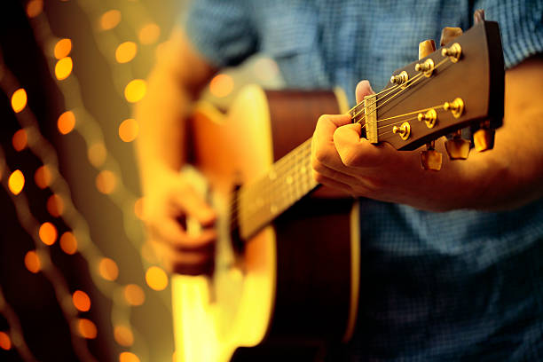 Man playing an acoustic guitar during a concert A DSLR photo of a man playing a guitar during a concert. The man is playing an acoustic guitar and wearing a blue shirt, the face is invisible. Some blured lights can be seen at the background. country and western music stock pictures, royalty-free photos & images