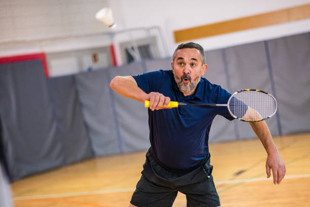 Man playing badminton Mature man hitting shuttlecock with badminton racquet in court. badminton stock pictures, royalty-free photos & images