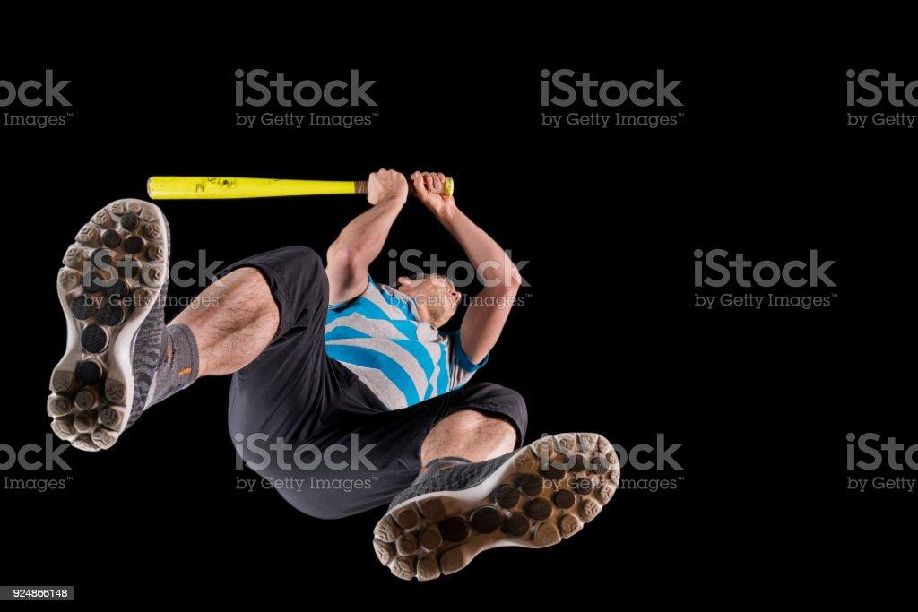 man plying baseball, studioshot, view bottom up