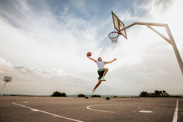 man playing basketball and doing a slam dunk - milan2099 stock photos and pictures
