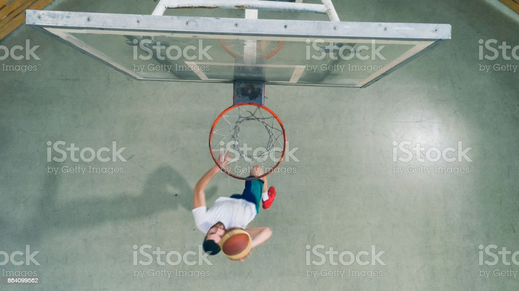 Man Playing Basketball in a school gym royalty-free stock photo