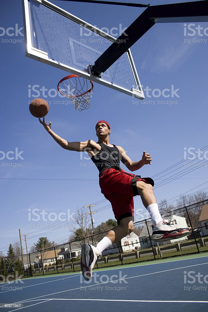 Man playing basketball on an outdoor court in mid jump royalty-free stock photo