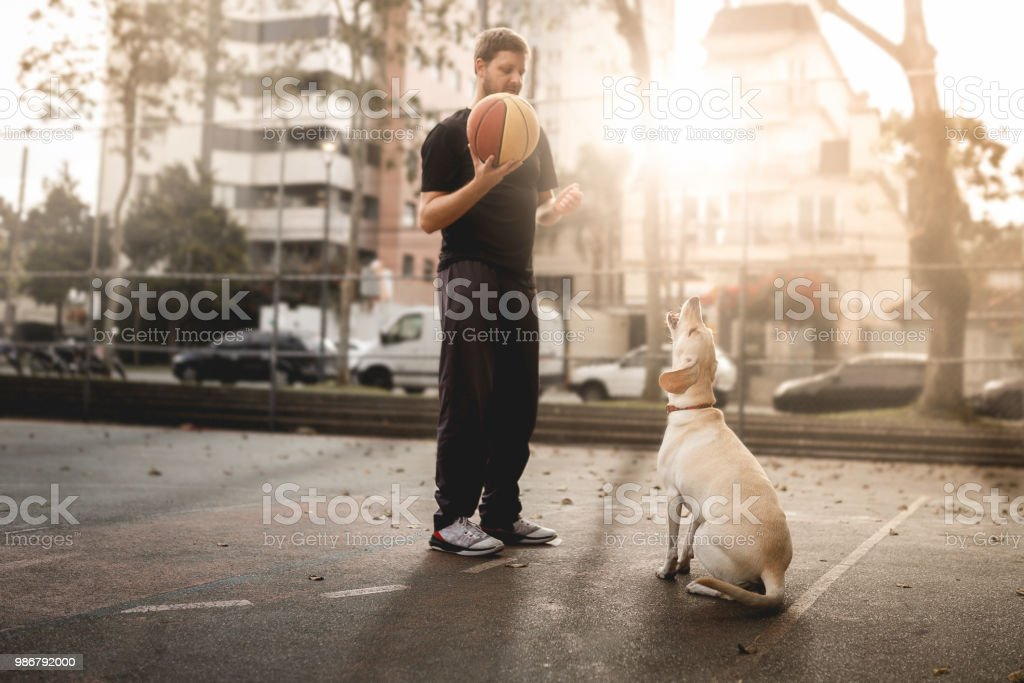 Man playing basketball with dog at public outdoor basketball court