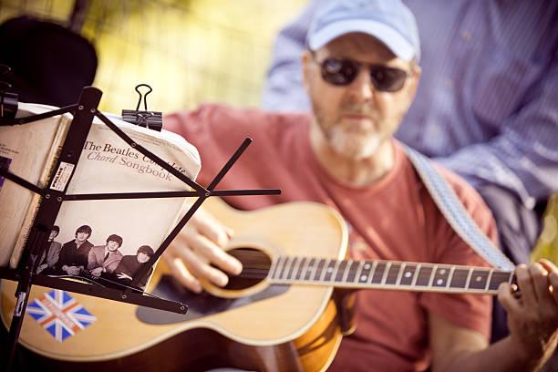 mann spielt beatles songs - beatles songs stock-fotos und bilder