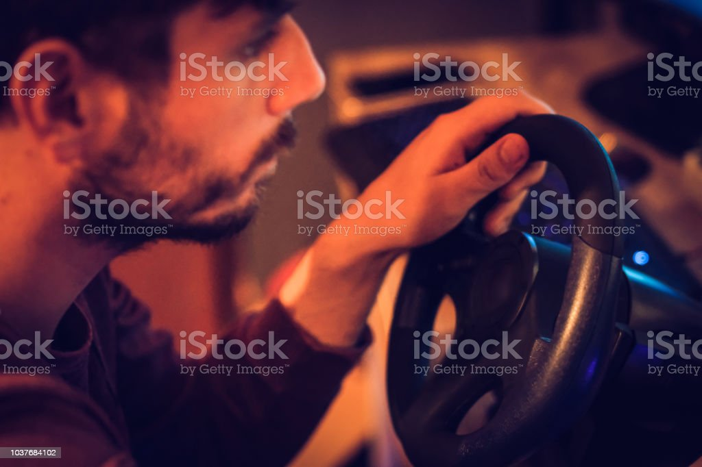 Man Playing Car Racing Video Game At Home Stock Photo
