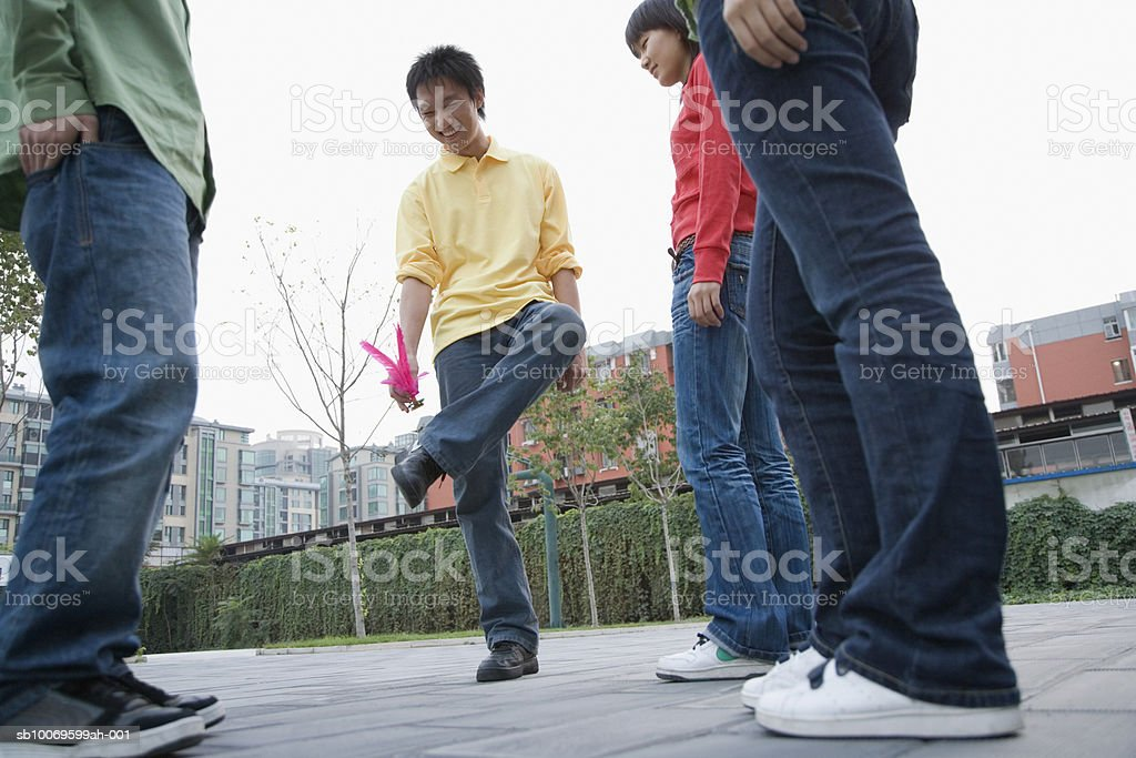 Man playing Chinese shuttlecock, friends watching, low angle view royalty-free stock photo