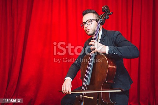 Young artist man  playing classical music on cello in stage.