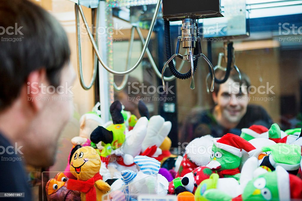 Man Playing Claw Game Machine stock photo