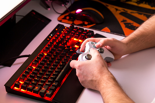 istock Man playing computer game on custom made desktop with joypad, keyboard, mouse. 659230824