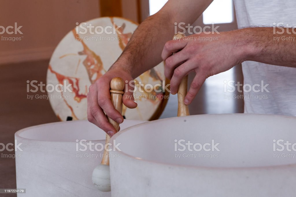 Man playing crystal bowl healing music Man sitting in indian with his two big crystal bowls and his native sacred drum, playing sacred music in a meditative state. Closeup shot Art Stock Photo