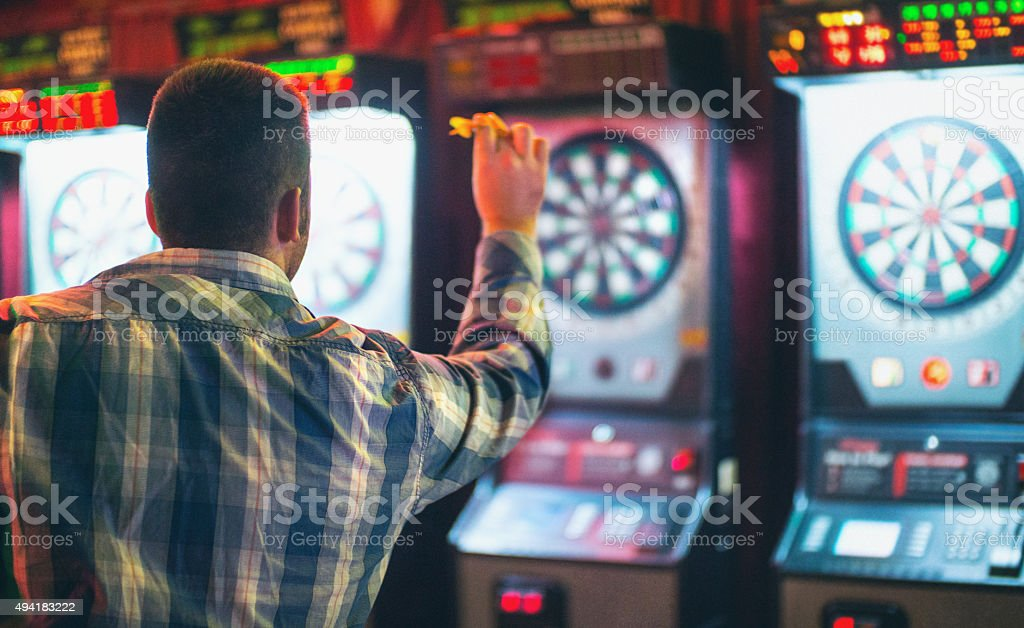 Man playing darts game. stock photo