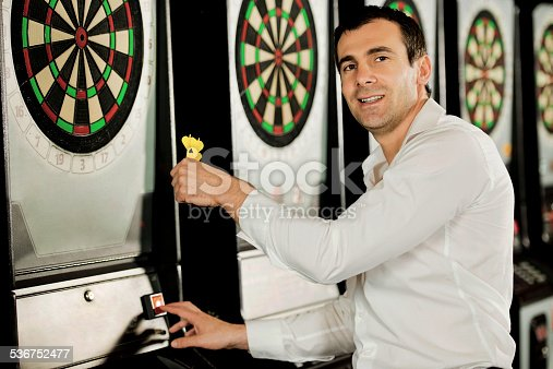 Mid adult woman taking the dart out of the dartboard. He is looking at the camera.