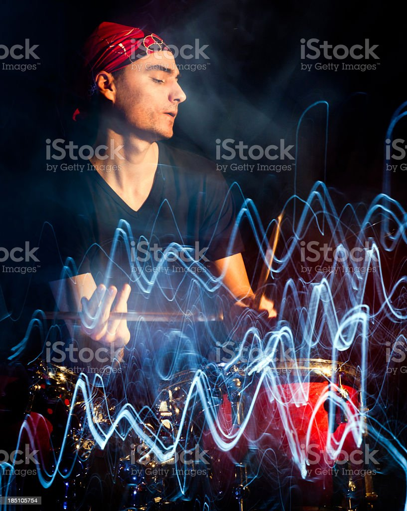 Man playing drums in dark with pulsating light trace stock photo