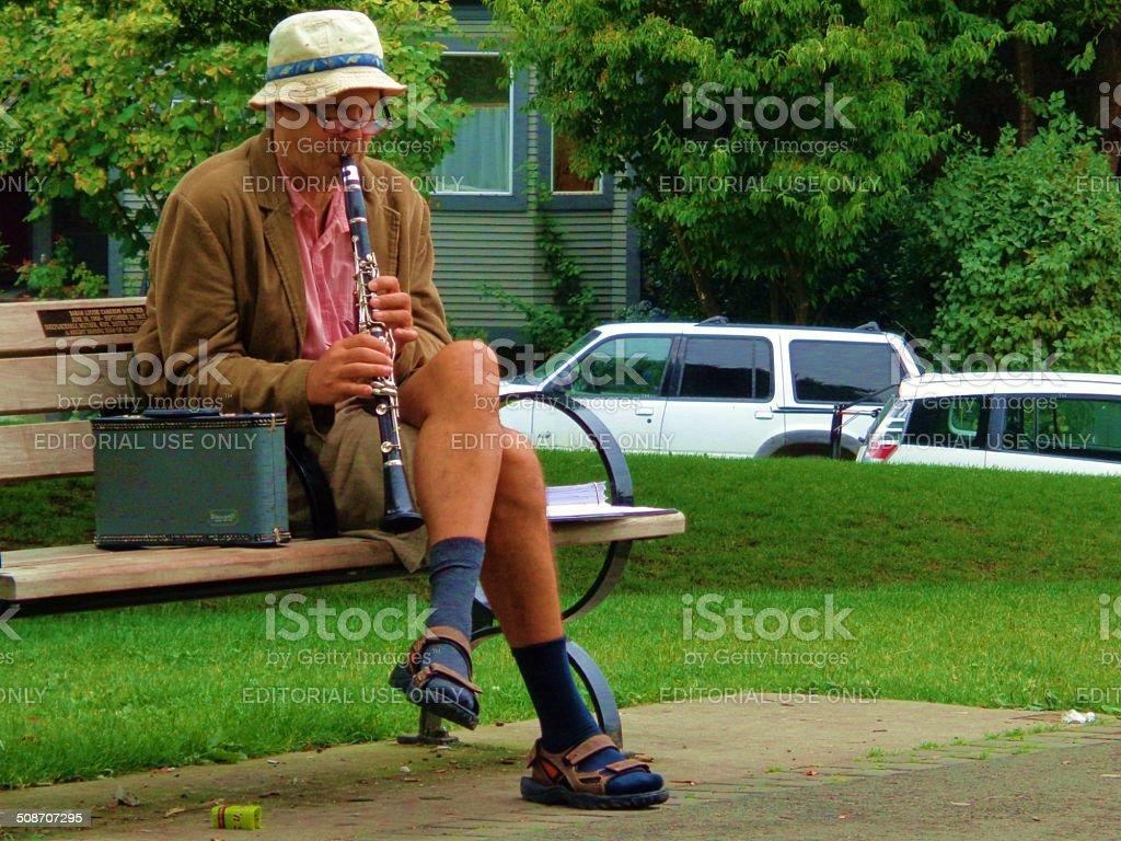 Man playing flute on park bench - horizontal stock photo