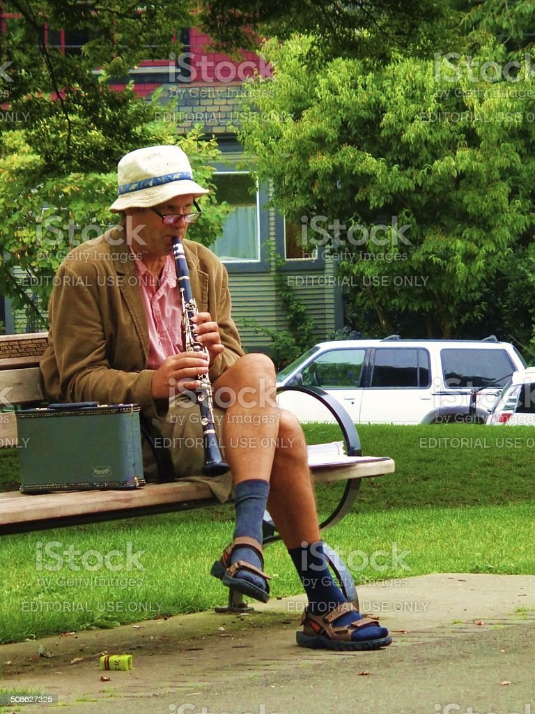 Man playing flute on park bench stock photo