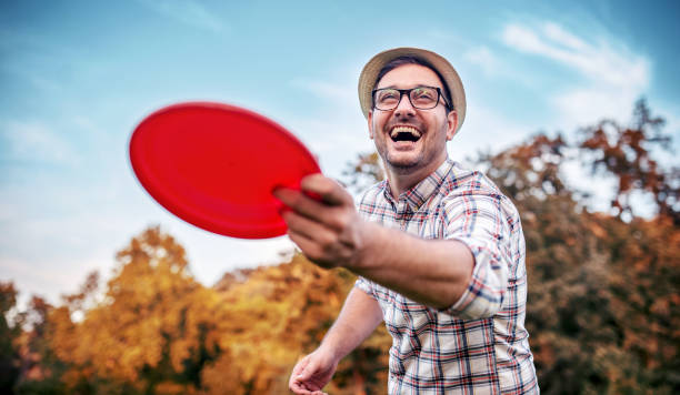 Man playing frisbee. Sport and recreation concept. Picnic time. Young man playing frisbee in the park. Sport and recreation concept. plastic disc stock pictures, royalty-free photos & images