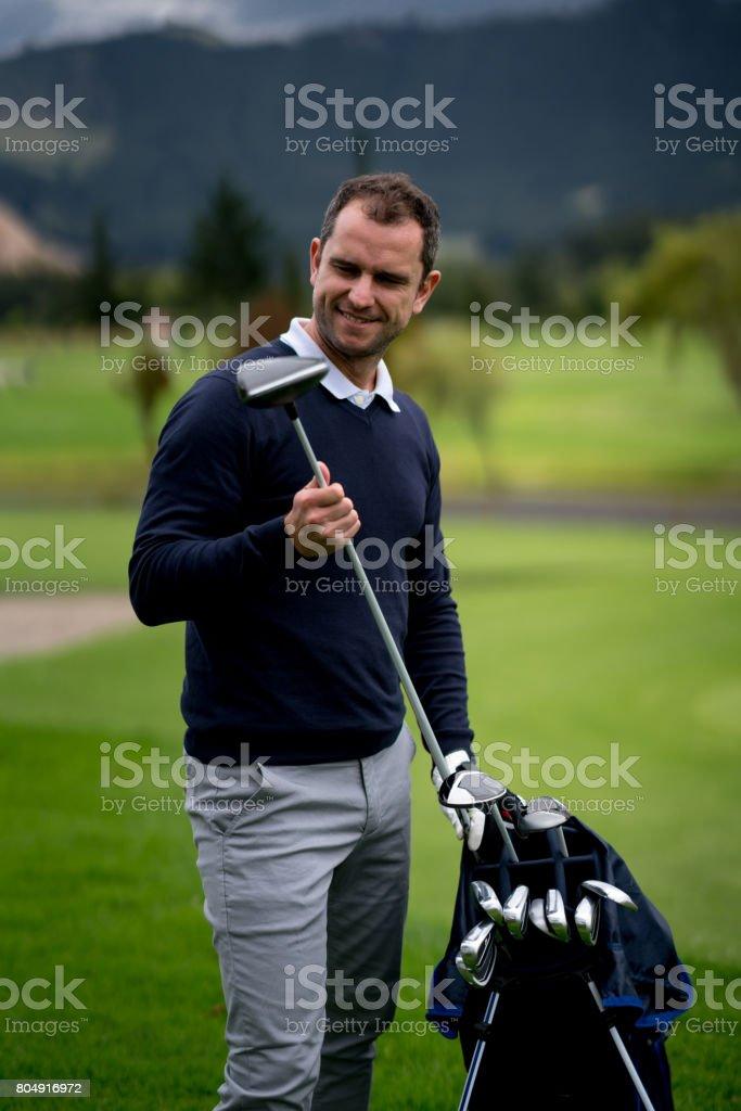 Man playing golf and choosing the club stock photo