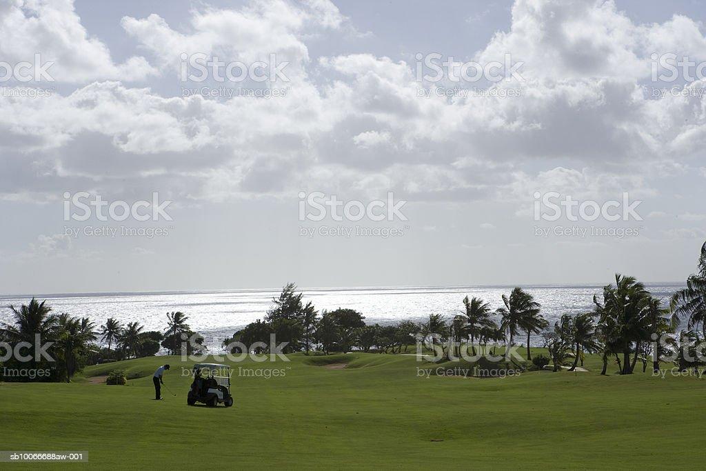 Homem jogando golfe, carrinho na Verde foto royalty-free