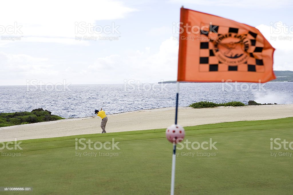 Man playing golf on golf course by sea royalty free stockfoto