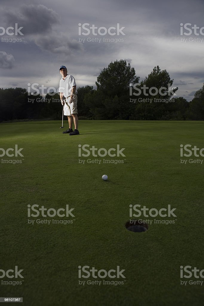 Man playing golf on golf course royalty-free stock photo