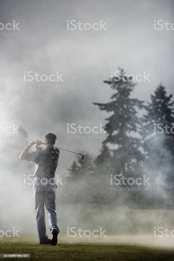 Man playing golf, rear view royalty free stockfoto