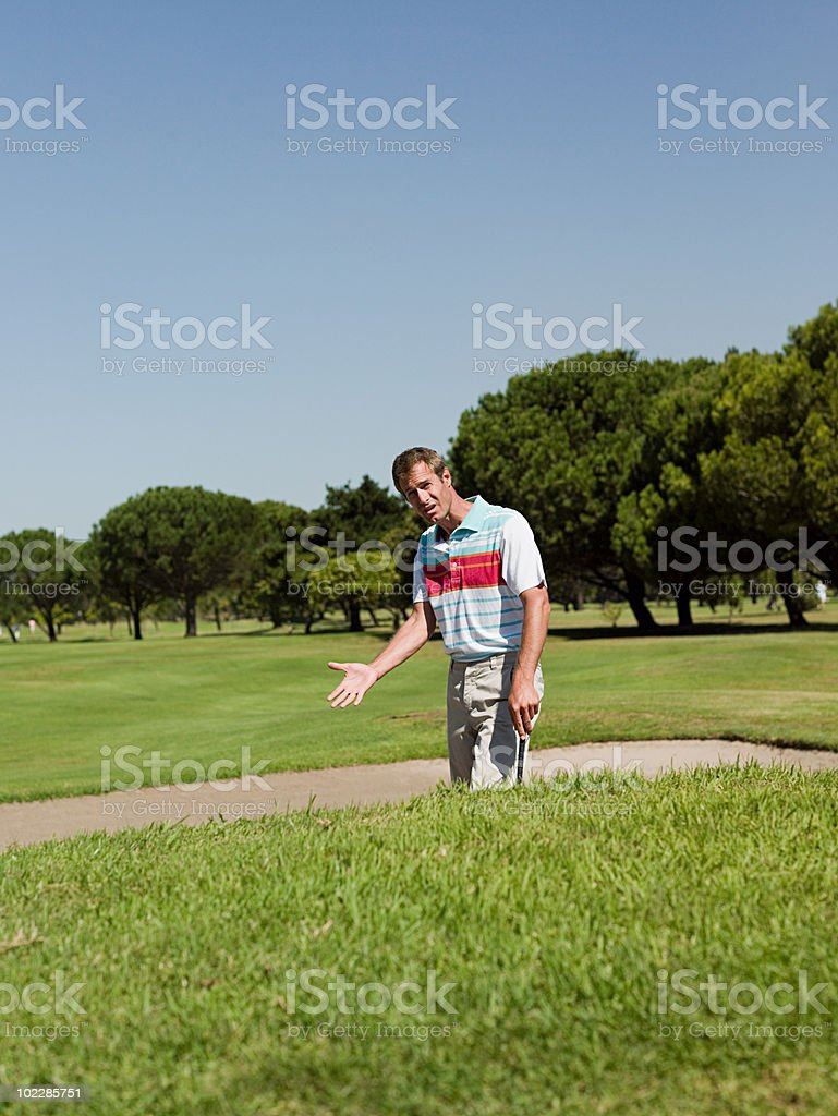 Man playing golf, stuck in bunker stock photo