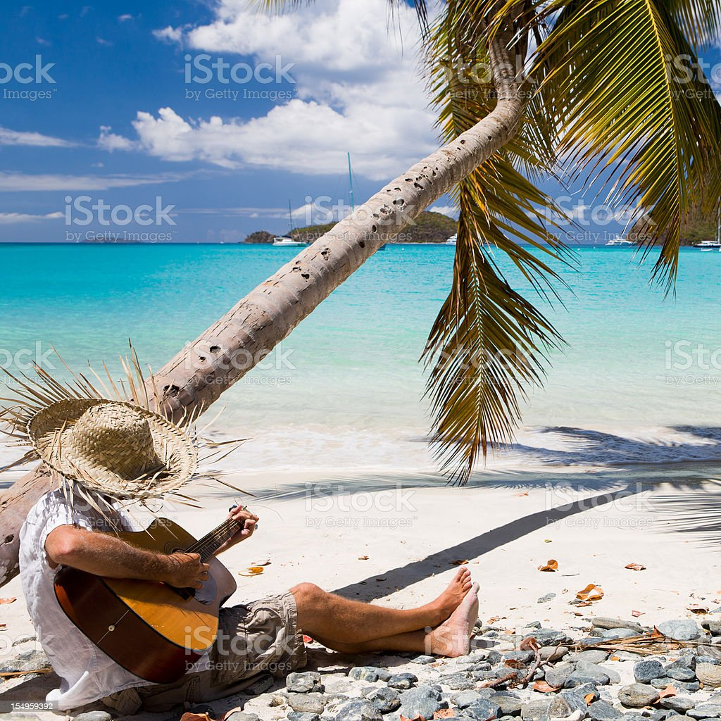 man playing guitar at a beach in the Caribbean stock photo