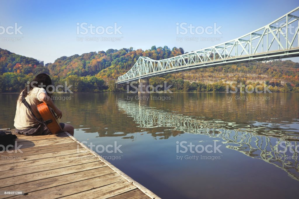 Man Playing Guitar by River A man writing songs on his acoustic guitar by the Sewickley Bridge that crosses the Ohio River in Pennsylvania. Adult Stock Photo
