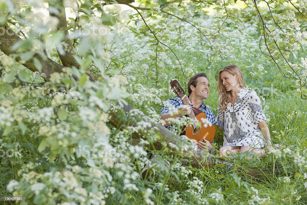 Man playing guitar for girlfriend in forest royalty-free stock photo