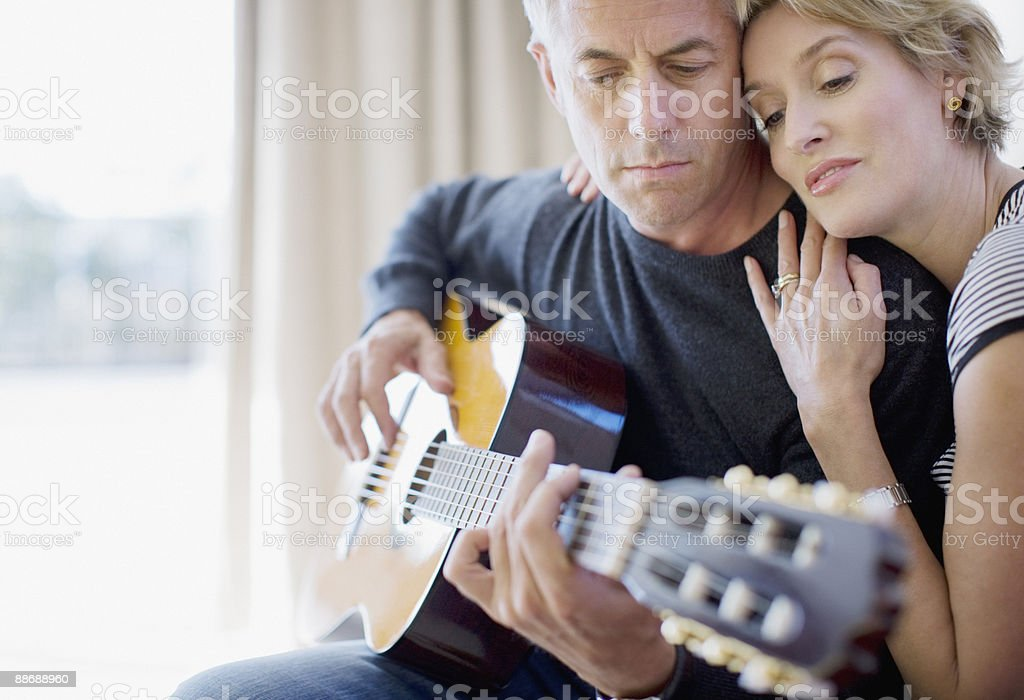 Man playing guitar for wife in living room royalty-free stock photo