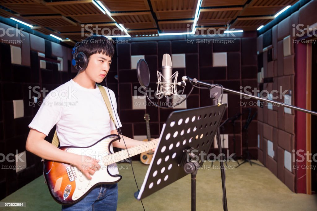 Adam bir kayıt stüdyosunda gitar çalmak royalty-free stock photo