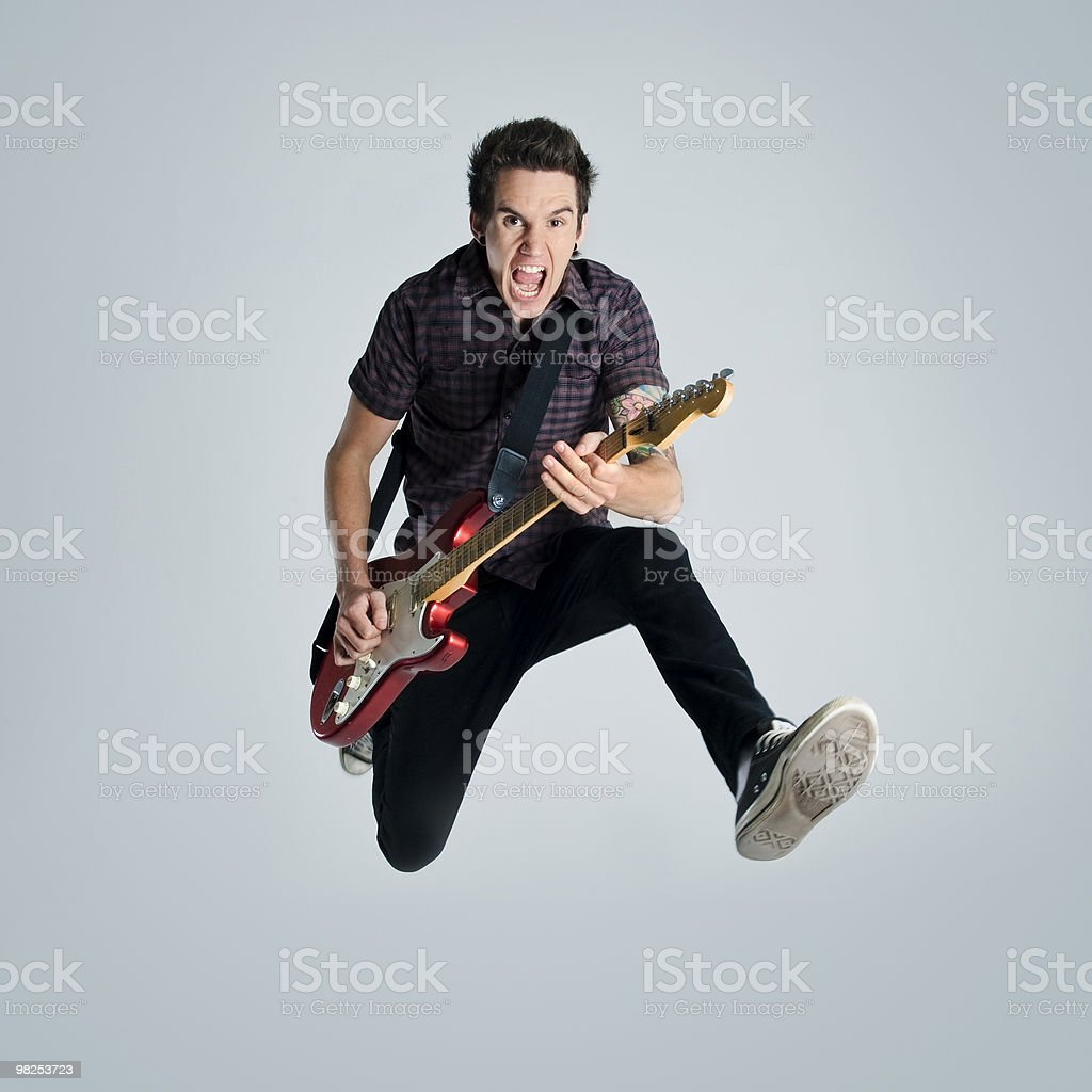 Man playing guitar jumping in the air stock photo