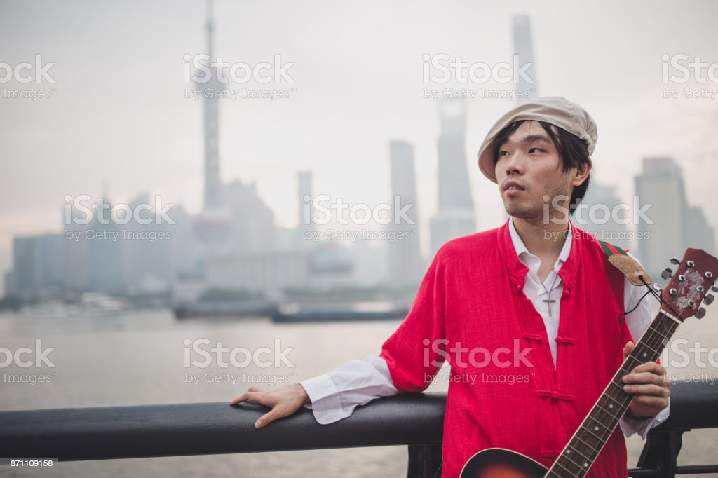 Man playing guitar near the river stock photo