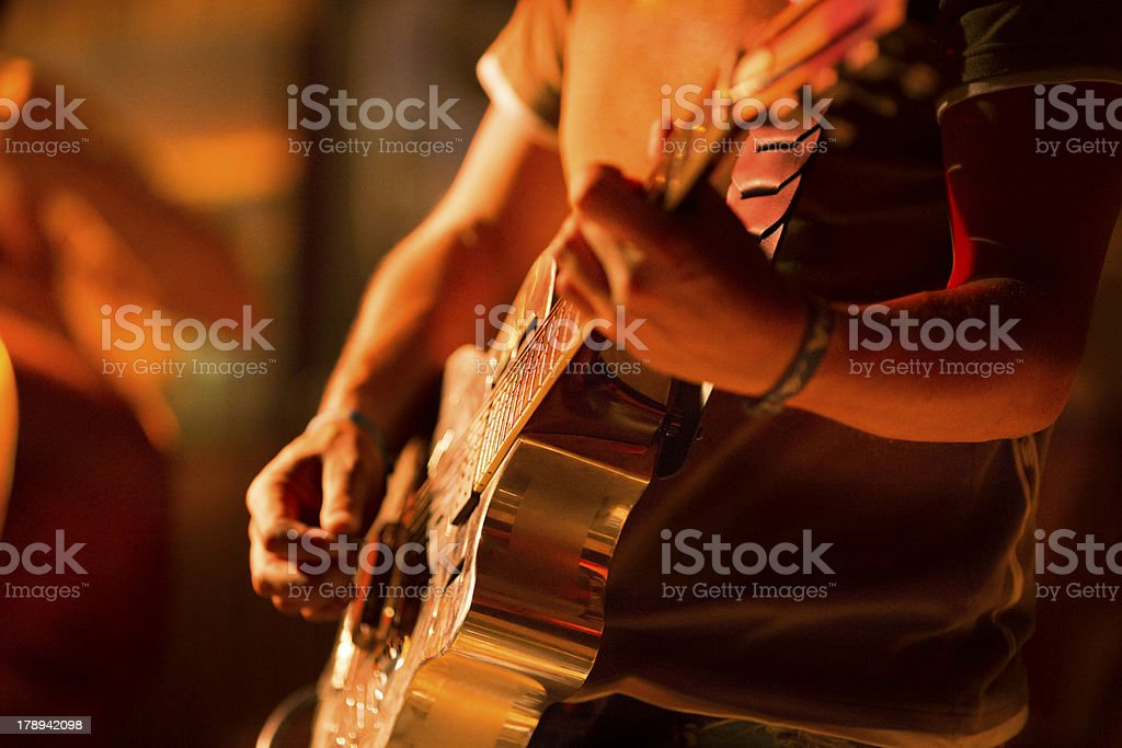 Man playing guitar on stage stock photo