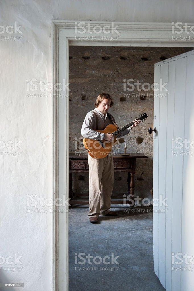 Man playing guitar, view through door stock photo