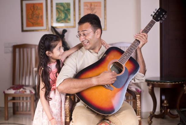 Mann spielt Gitarre mit Tochter zu Hause – Foto