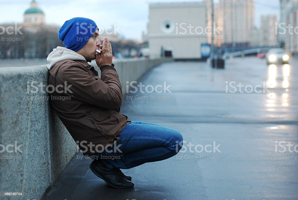 man playing harmonica on the street stock photo