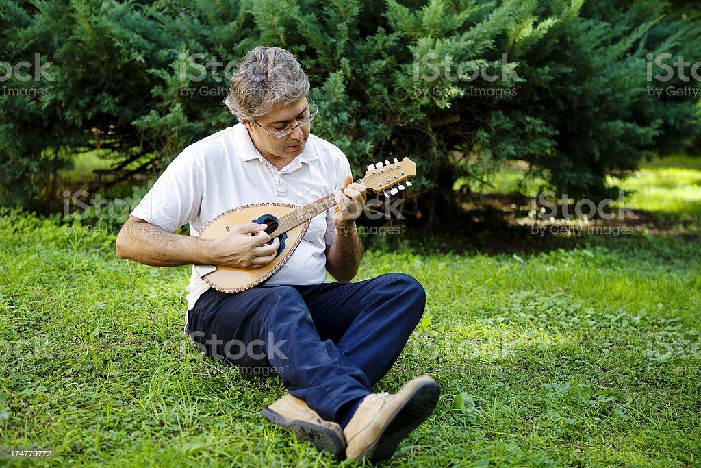 Man Playing Mandolin Outdoors royalty-free stock photo